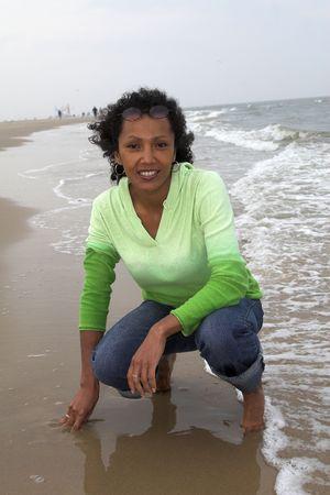 woman kneeling: Pretty black woman kneeling by the edge of the waterside