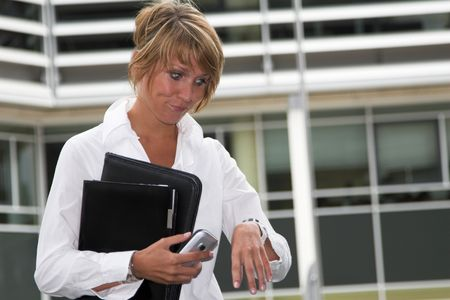 Businesswoman pulling a face when looking at her watch photo