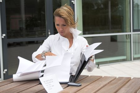 annoyance: Businesswoman sitting outdoors with her notes and trying to control the paper blowing in the wind