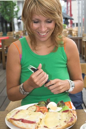 just arrived: Pretty blond girl sitting outdoors on a terrace and looking very happy with her food that just arrived Stock Photo
