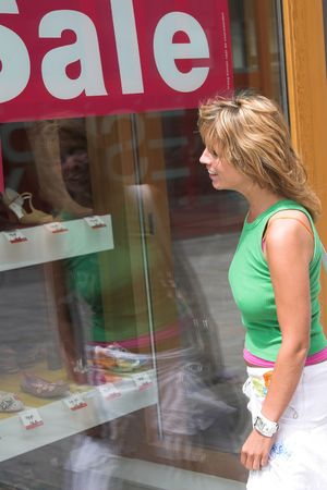 tempted: Pretty blond woman windowshopping in a shoestore