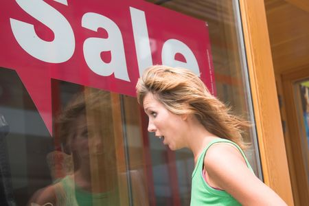 departmentstore: Pretty blond woman looking totally shocked when looking in the window of the shoestore with summersale