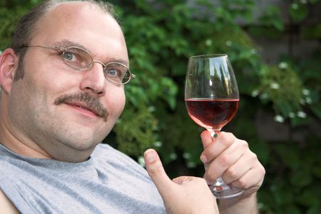 Handsome mature man enjoying a glass of rose in the garden photo
