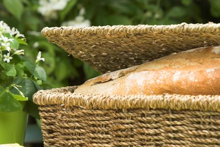 Loaf of bread in a straw basket for the picknick