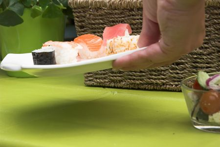 picknick: Hand reaching to the table to add a plate of sushi for the picknick lunch for that afternoon (shallow dof)