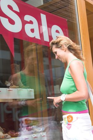 departmentstore: pretty blond woman checking out the window of a shoestore that has a summersale going on