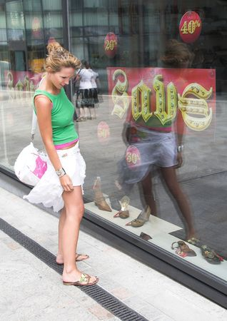 departmentstore: Pretty girl checking out the window of a shoestore that promises a 70% discount Stock Photo