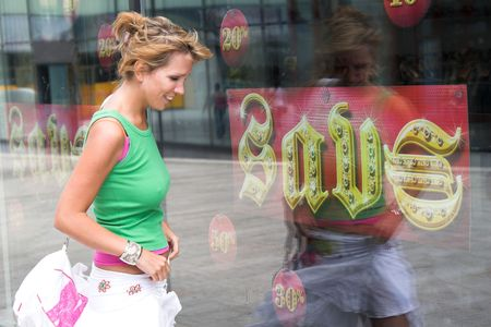 departmentstore: Pretty blond girl being tempted by the savings signs of the shoestore Stock Photo