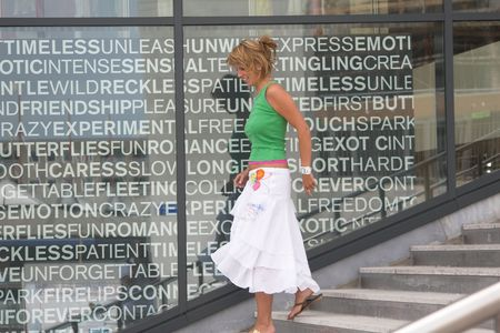 departmentstore: Pretty blond girl walking down the stairs in a shopping area (text on the window is not a brand) Stock Photo