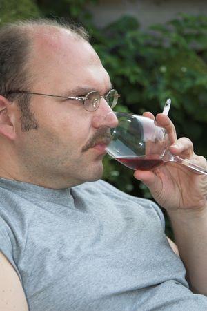 sorbo: Madure a hombre balding que toma un sip de su cristal de vino mientras que sostiene un cigarrillo en su mano