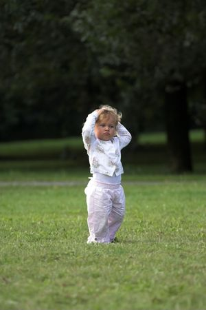 behaving: Little two year old girl behaving like a grownup in the park Stock Photo