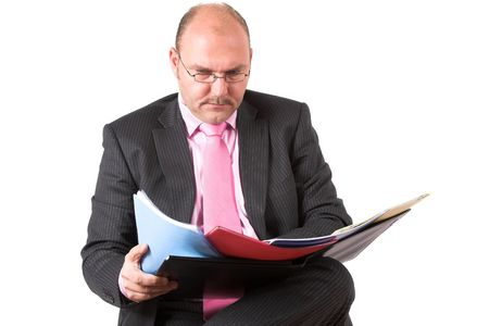 Businessman putting some of his files next to eachother to compare the numbers Stock Photo