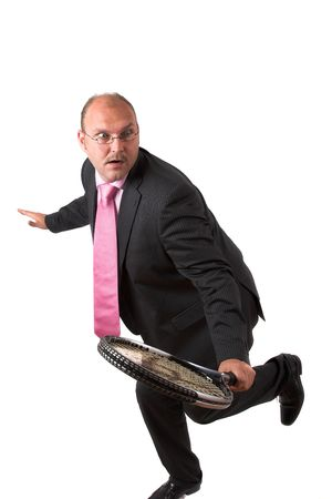 Businessman in suit balancing on one leg while about to hit with his racket photo