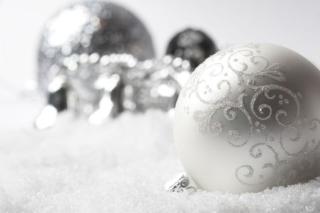 Christmas bauble lying in fake white snow with decorations in the background