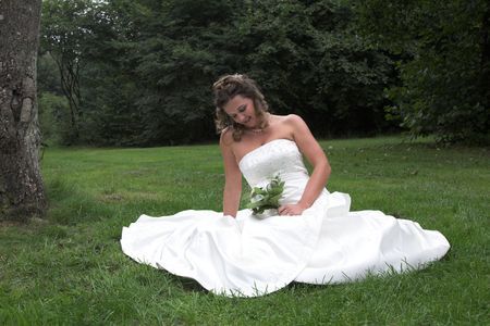 Beautiful bride sitting on a field photo