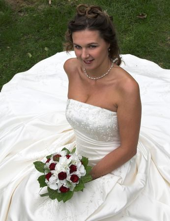 Beautiful bride sitting on the grass photo
