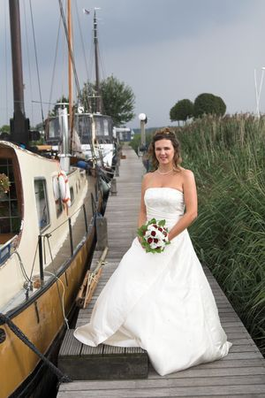 Beautiful bride standing near the boats with thunderclouds forming in the background photo