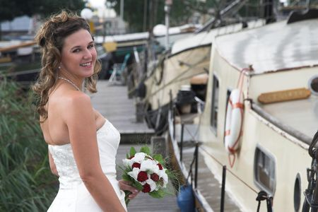 Beautiful smiling bride standing on the boardwalk photo