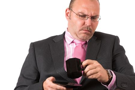 sip: Businessman looking into his coffeecup with a disgusted look, his mouth still full with first sip