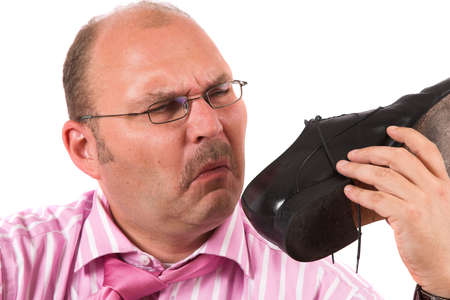 Businessman puling a face of disgust while holding his shoe close to his nose photo
