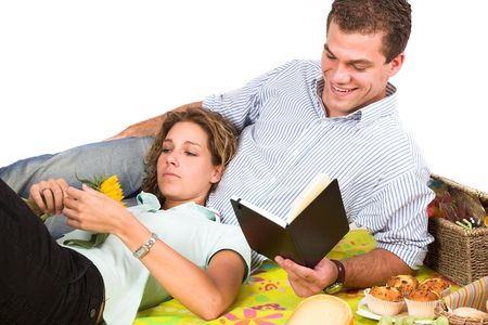 Couple having a picnic and relaxing while the man is reading in a book