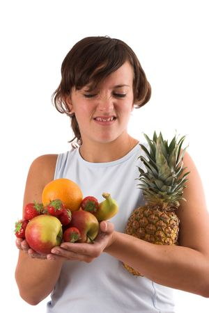 Young woman holding a pile of various fruits in her hands and pulling a face as if she doesnt really like it photo