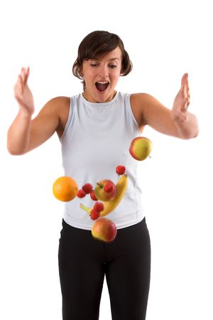 Pretty brunette dropping all the fruit from her hands. Fruit is hanging in midair photo