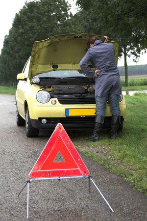 sich b�cken: H�bsche brunette Schlaufe �ber den Inneren ihres Autos (Fokus auf dem M�dchen) mit Gefahrdreieck in der Frontseite