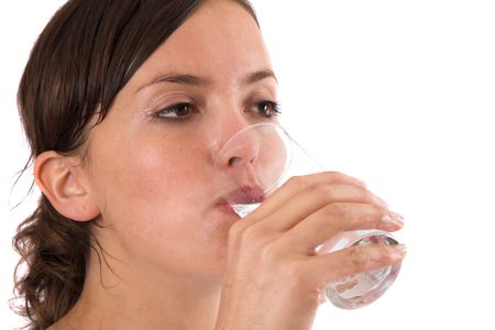 replenishing: Pretty brunette still sweaty from her workout drinking a glass of water to replenish her fluids Stock Photo