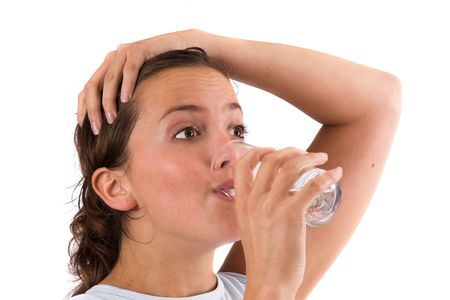 replenishing: Pretty brunette drinking a glass of water after her workout