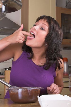 licking finger: Pretty brunette putting her finger covered in chocolate into her mouth