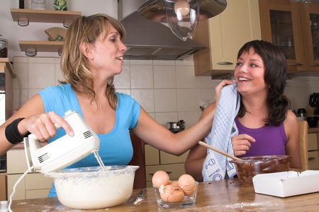 Two girls cooking together while one is having chocolate on her face. The other girl is wiping it away with a dishcloth photo