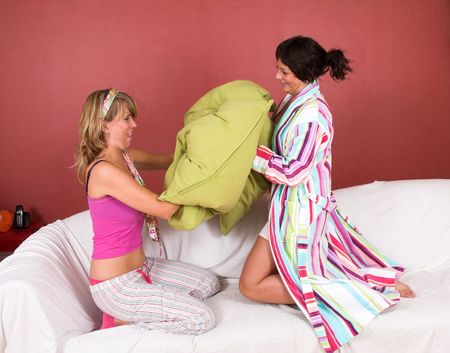 Two girls having a pillow fight on the couch photo