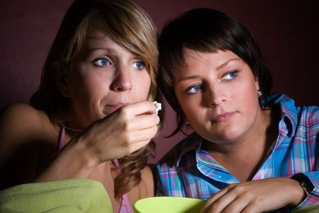 snacking: Two girls watching a scary movie together while eating popcorn