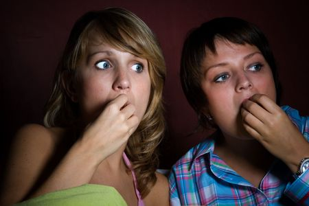 Two girls close together watching a scary movie just illuminated by the light of the tv photo