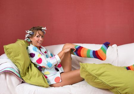 Girl with her hairin hot rollers and pulling on her funny colorful socks photo