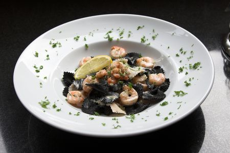 seafruit: Big plate filled with black pasta with tigerprawns and regular small shrimps; plate is decorated with parsley