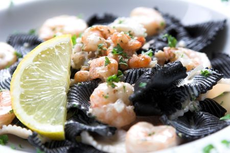 seafruit: Delicious pasta dish with big tigerpraws and a lemon ready to be squeezed Stock Photo