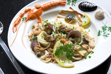 seafruit: Delicious dish with spaghetti, mussels and squid served on a colorfull seafood plate