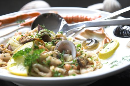 Delicious seafood dish served with shells, shrimps, squid and a slice of lemon on a colorfull plate Stock Photo - 608012