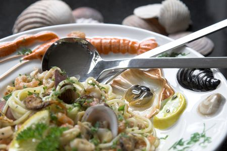 seafruit: Seafood pasta dish served on a colorfull plate with shells, mussels and shrimps