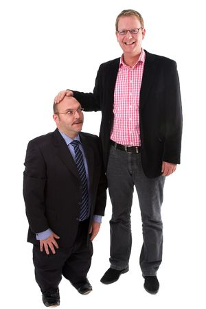 Two businessman standing on white background while one is putting his hand on the smaller mans head photo