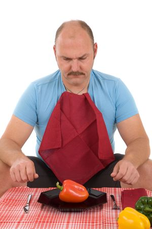 Overweight man sitting at the table with knife and fork and a pepper on his plate photo