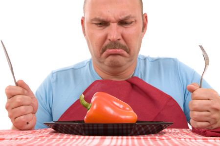 Overweight man with healthy vegetable on plate looking unhappy (focus on pepper) photo