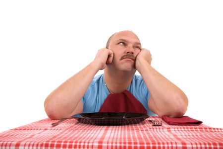 demotivated: Overweight man looking very unhappy with empty plate in front of him Stock Photo