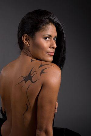 Beautiful brazilian woman sitting a bare back and a tattoo  Stock Photo - 2995652