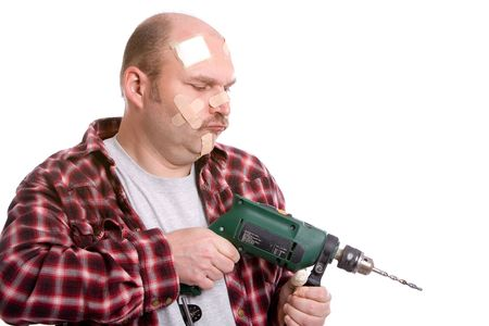Mature man trying to drill something covered in bandaids photo