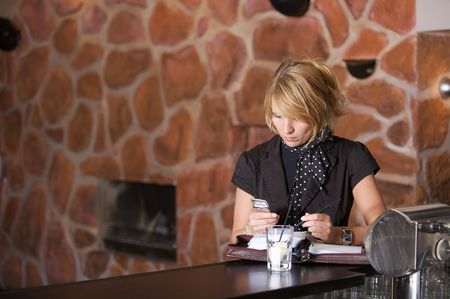Beautiful blond businesswoman standing in the bar with her mobile and notebook photo