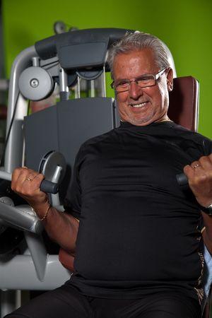 Senior man doing strenuous exercise on the machines Stock Photo - 6525108