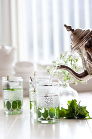 Freshly made minttea being pouring into a glass Stock Photo